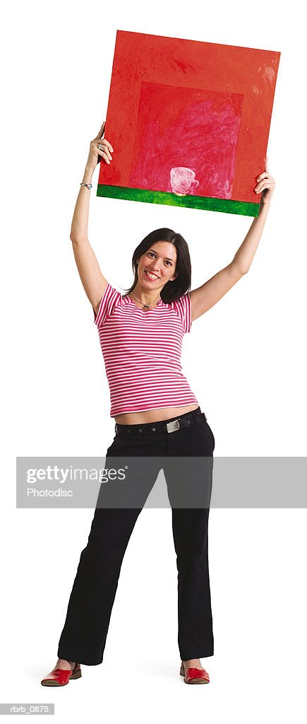 silhouette of a young caucasian woman as she poses with her painting above her head : Stockfoto