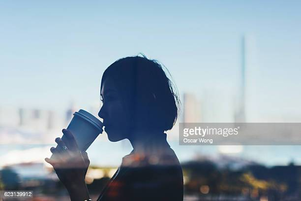 Silhouette of a young lady drinking coffee