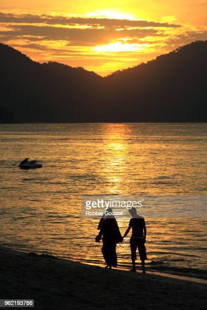 silhouette of a young muslim couple holding hands while walking along the beach at sunset. - honeymoon stock photos and pictures