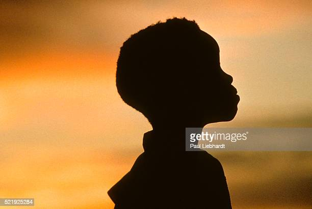 A silhouette of a young West African girl at sunset