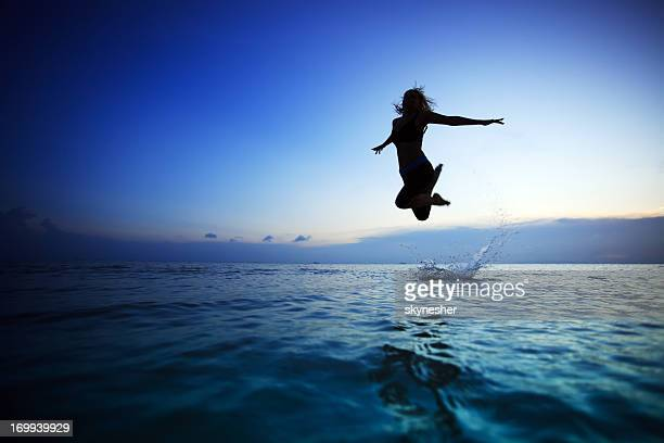 Silhouette of a young woman jumping in the water