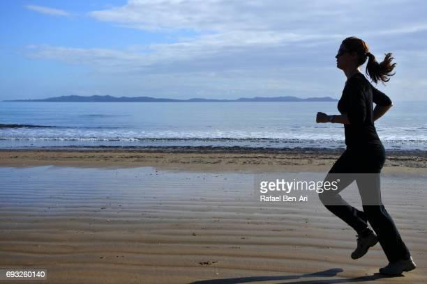 silhouette of a young  woman running on the beach - rafael ben ari stock-fotos und bilder