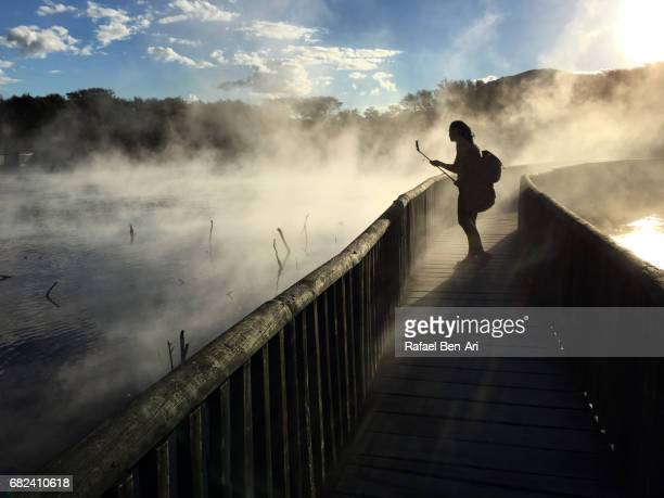 Silhouette of a young woman takes a selfie with hot pools in Rotorua New Zealand