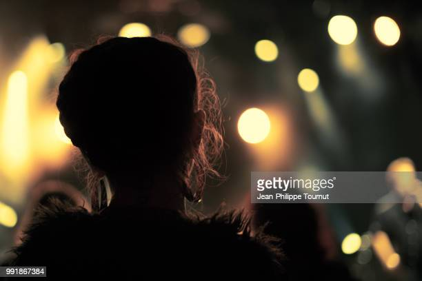 silhouette of a young woman watching a concert - performance stock pictures, royalty-free photos & images