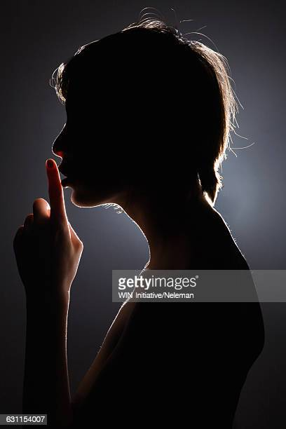 Silhouette of a young woman with her finger on her lips