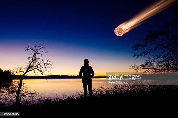 Silhouette of adult watching meteor falling in night sky
