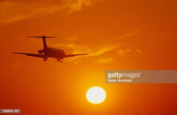 silhouette of aeroplane against orange sunset - rainer grosskopf stock pictures, royalty-free photos & images