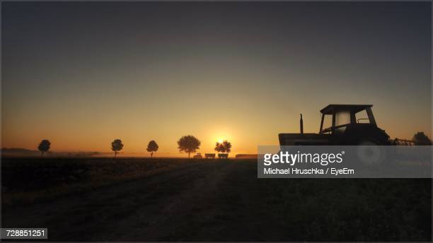 silhouette of agricultural field against clear sky during sunset - michael hruschka stock-fotos und bilder