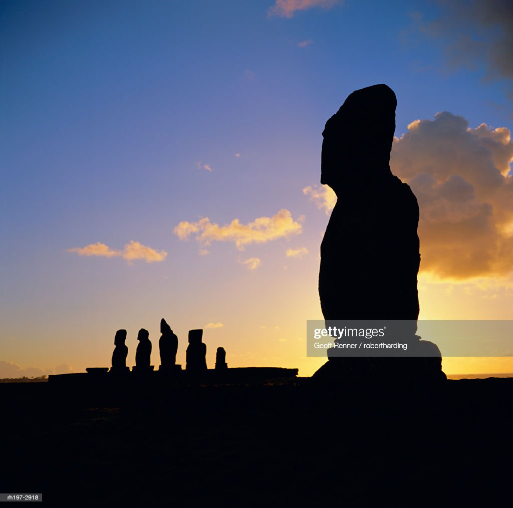 Silhouette of Ahu Tahai in foreground and behind the five moai (statues) of Ahu Vai Uri, Easter Island, Chile : Foto de stock