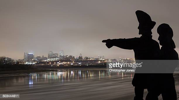 Silhouette of American explorers Meriweather Lewis and William Clark point toward the Kansas City, Missouri skyline on an overcast and foggy winter...