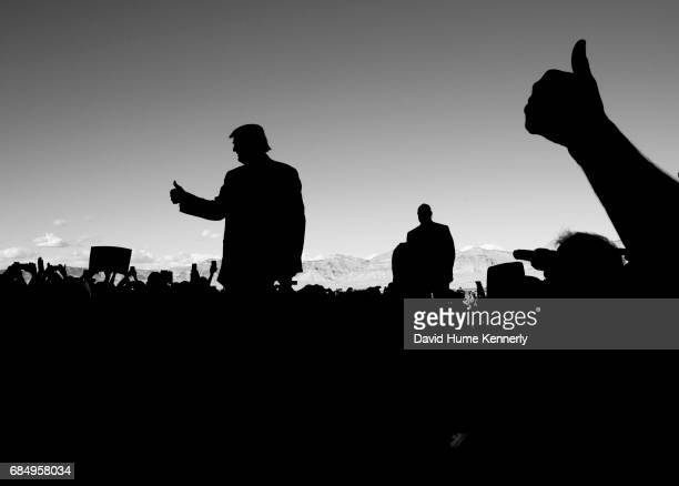Silhouette of American real estate developer and presidential candidate Donald Trump as he gives a 'thumbs up' sign to supporters at a campaign rally...