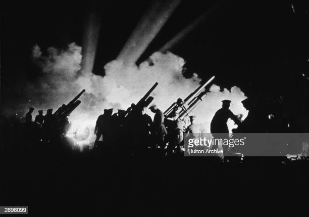 Silhouette of American soldiers manning 3inch antiaircraft gun batteries as spotlights search the night skies for incoming planes during World War I
