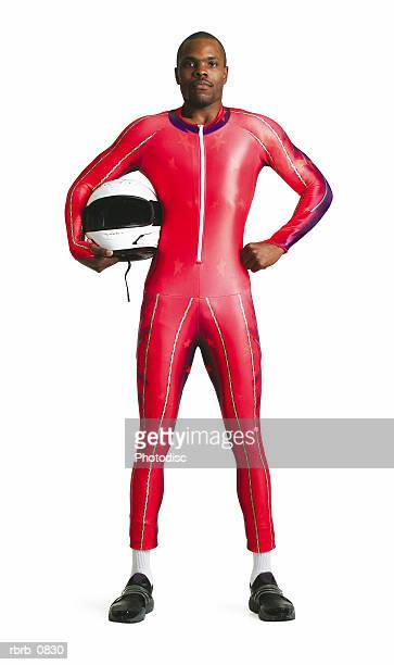 silhouette of an adult african american male athlete as he stands in his training suit with his helmet under his arm