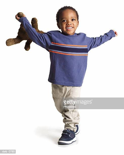 silhouette of an african american little boy in  a blue shirt as he runs with his teddy bear
