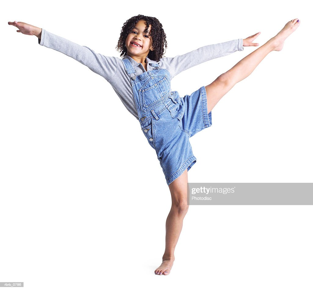 silhouette of an african american little girl in denim overalls as she kicks up high into the air : Stockfoto