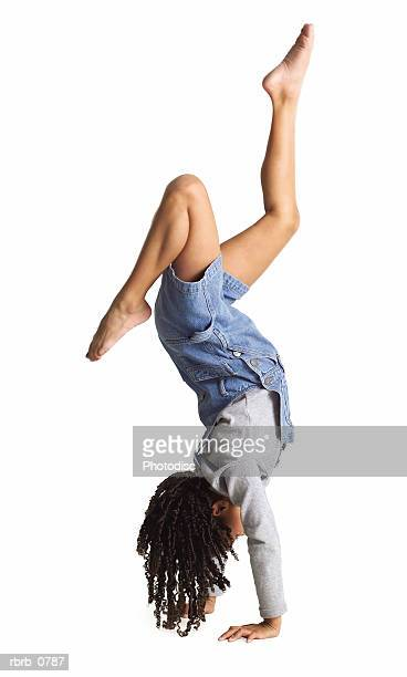 silhouette of an african american little girl in denim overalls as she does a hand stand