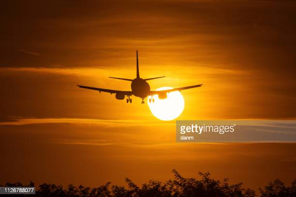 silhouette of an air plane over the sun with beautiful red clouds in background - airplane part stock photos and pictures
