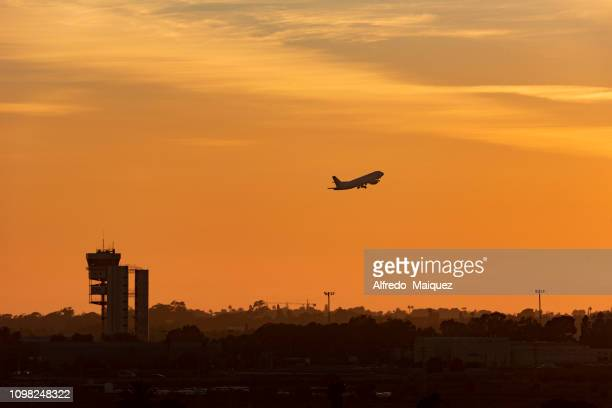 silhouette of an airplane and control tower just after take off during sunset, alicante/elche international airport, alicante,spain, europe - alicante stock pictures, royalty-free photos & images