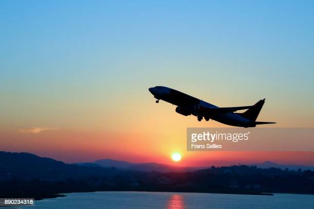 silhouette of an airplane just after take off during sunset - aeroplane stock photos and pictures