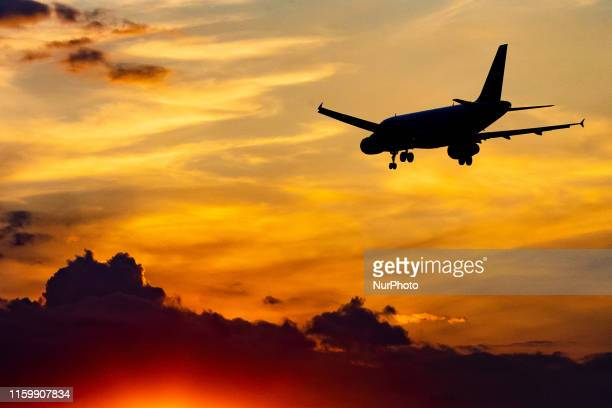 Silhouette of an airplane landing on final approach during the sunset at London Heathrow International Airport EGLL LHR in England UK The aircraft is...