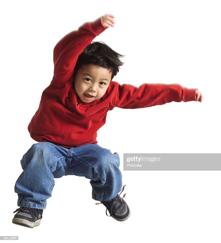 silhouette of an asian male child in jeans and a red shirt as he jumps sideways through the air : Stockfoto