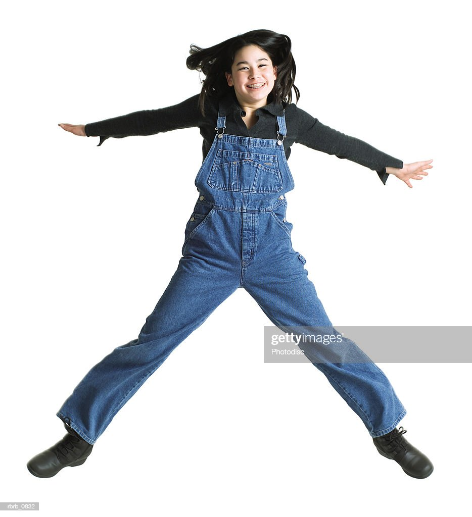 silhouette of an asian teenage girl in denim overalls as she jumps up into the air : Stockfoto