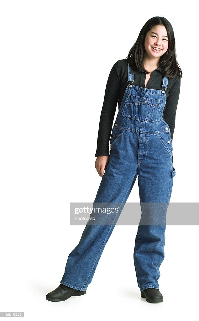 silhouette of an asian teenage girl in denim overalls as she smiles at the camera : Foto de stock