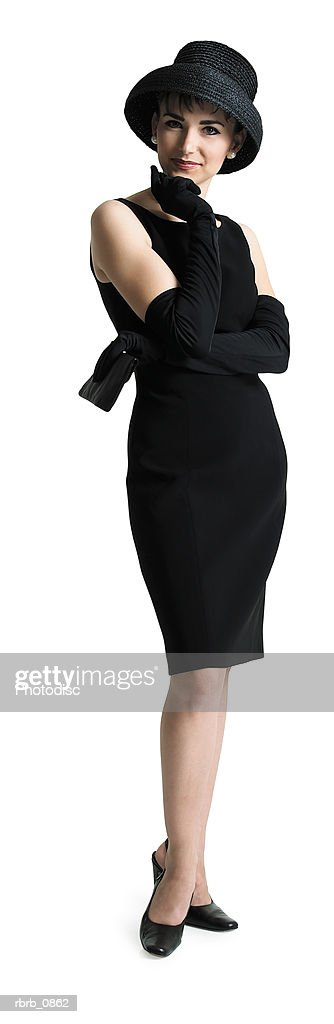 silhouette of an attractive sophisticated caucasian woman in a black dress and hat as she smiles at the camera : Stock Photo