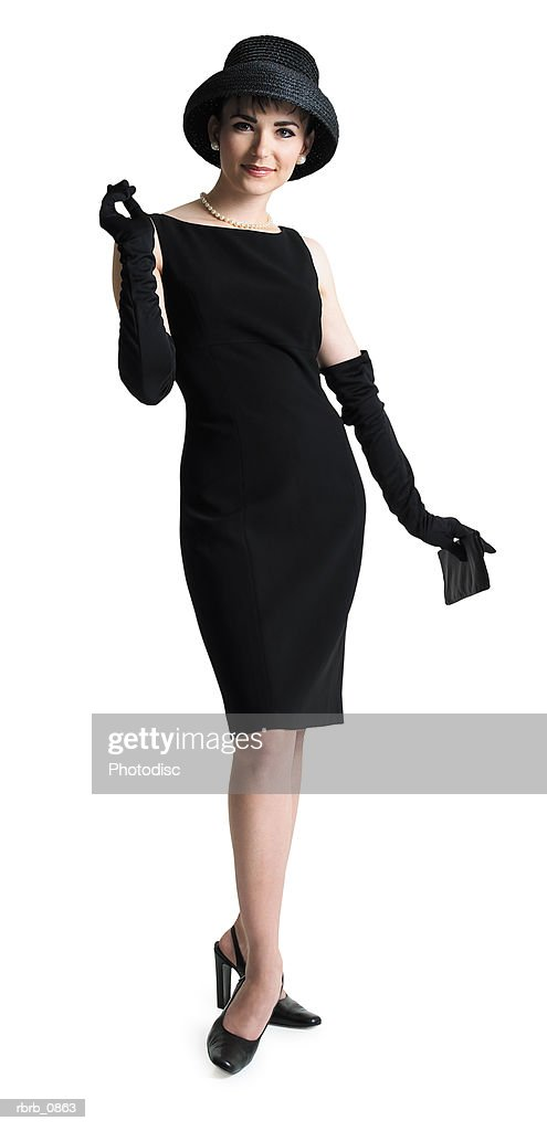 silhouette of an attractive sophisticated caucasian woman in a black dress and hat as she smiles at the camera : Stockfoto