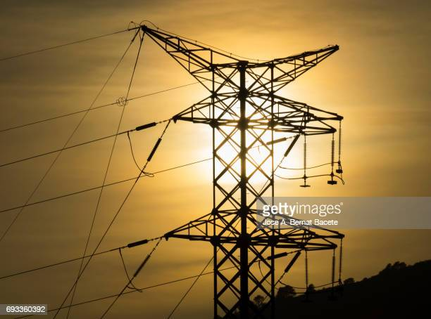 Silhouette of an electrical tower of high tension on the top of a mountain to the late afternoon with a sky orange color and the sun