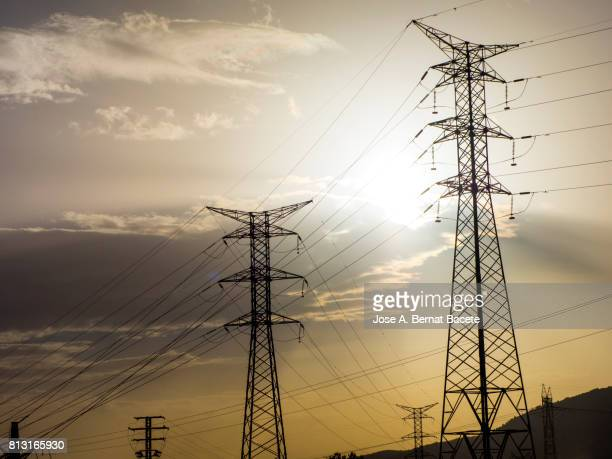 Silhouette of an electrical towers of high tension on the top of a mountain to the late afternoon with a sky orange color and the sun