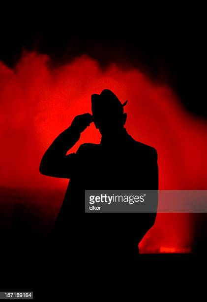 silhouette of an elegant man against colorful fountain at night. - hat stock photos and pictures