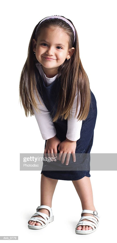 silhouette of an ethnic little girl as she puts her hands on her knees and smiles : Stockfoto