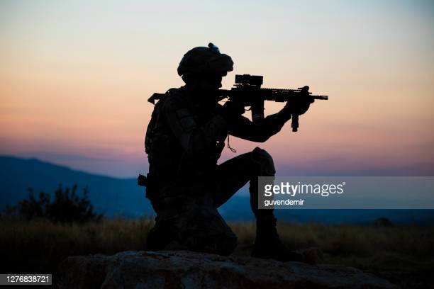silhouette of an kneeling turkish soldier shooting at target at sunset - terrorism stock pictures, royalty-free photos & images
