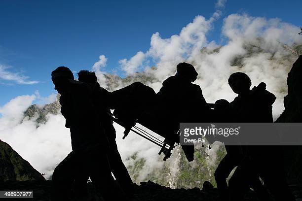 CONTENT] A silhouette of an old lady being carried in a chair by porters up the steep winding path to the Hemkund Sahib Gurudwara in the Himalayas...