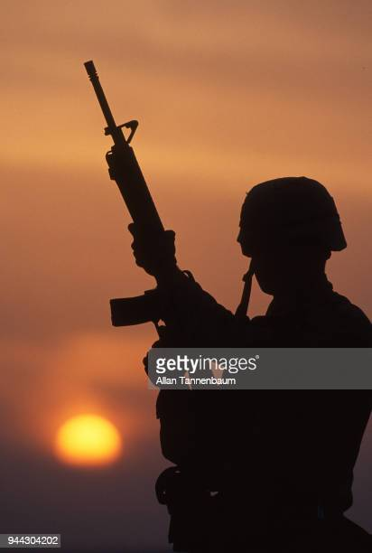 Silhouette of an unidentified American soldier seen against the setting sun during the Gulf War Iraq 1991