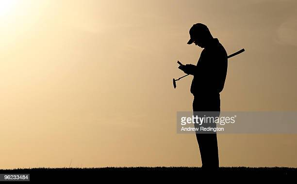 A silhouette of Andrew Coltart of Scotland as he checks his scorecard on the tenth hole during the first round of the Commercialbank Qatar Masters at...