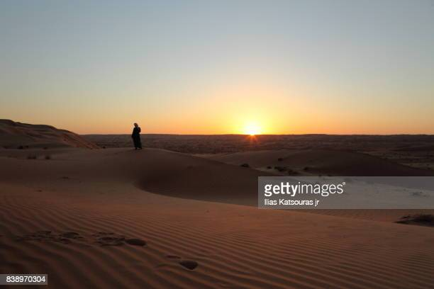 Silhouette of Arab man in desert at sunset