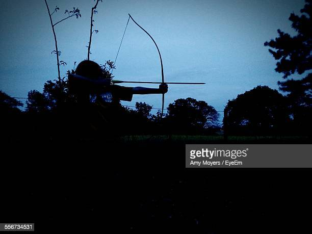 silhouette of archer aiming bow and arrow - longbow stock photos and pictures