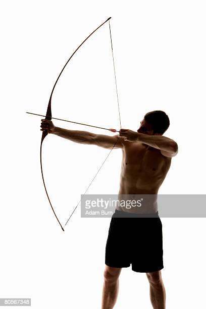 silhouette of archer pulling an arrow back on his longbow - arco arco e flecha - fotografias e filmes do acervo