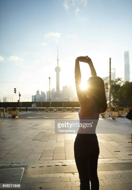 Silhouette of Asian woman say Good Morning to Shagnhai at Huangpu River riverside with Shanghai downtown in background, China.