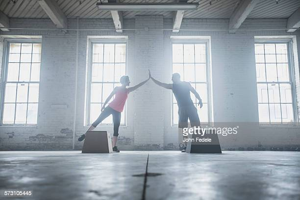 Silhouette of athletes high-fiving near platforms
