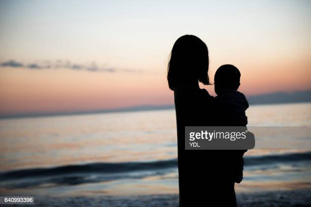 A Silhouette of Baby and Mother in the sunset ocean.