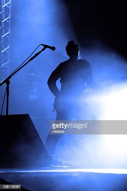 シルエットをバンドメンバーがギターを弾いている