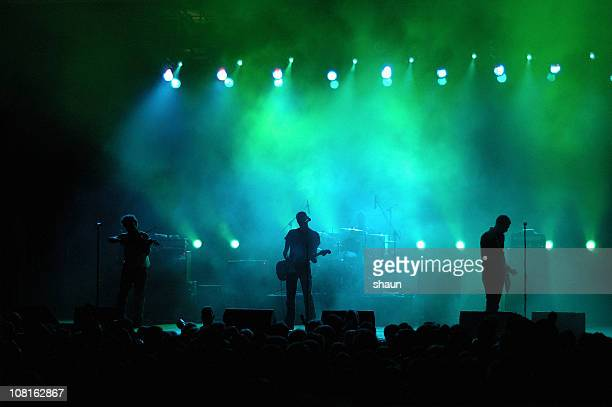 Silhouette of Band on Stage in Colored Lighting