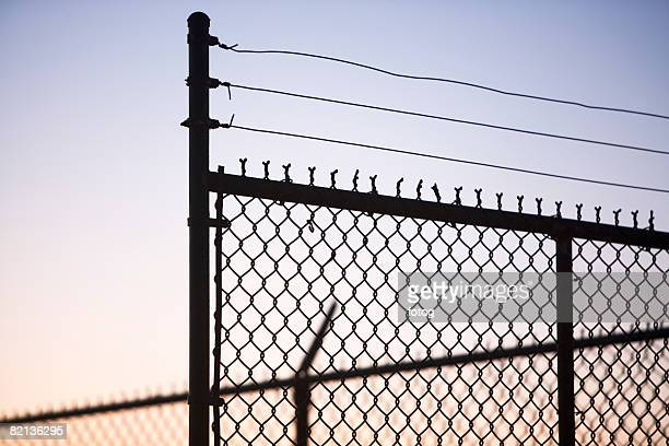 Silhouette of barbed wire and chain-link fence