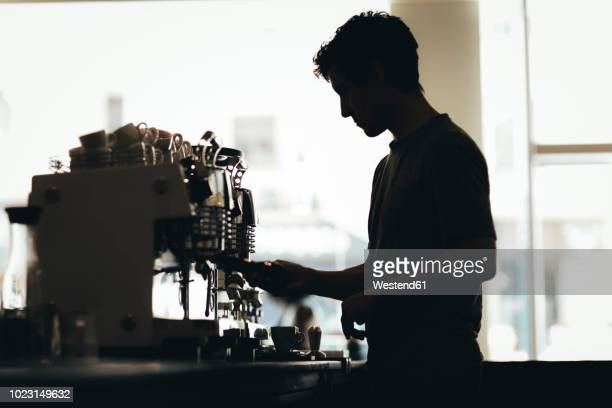 silhouette of barista preparing coffee in a coffee bar - wait staff stock pictures, royalty-free photos & images