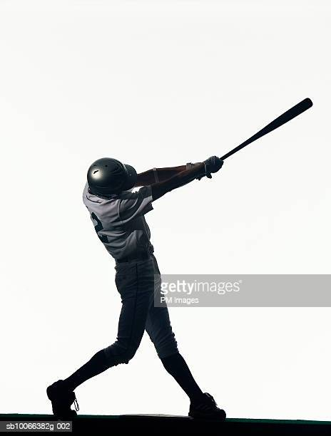 silhouette of baseball batter swinging bat, side view - baseball player stock pictures, royalty-free photos & images