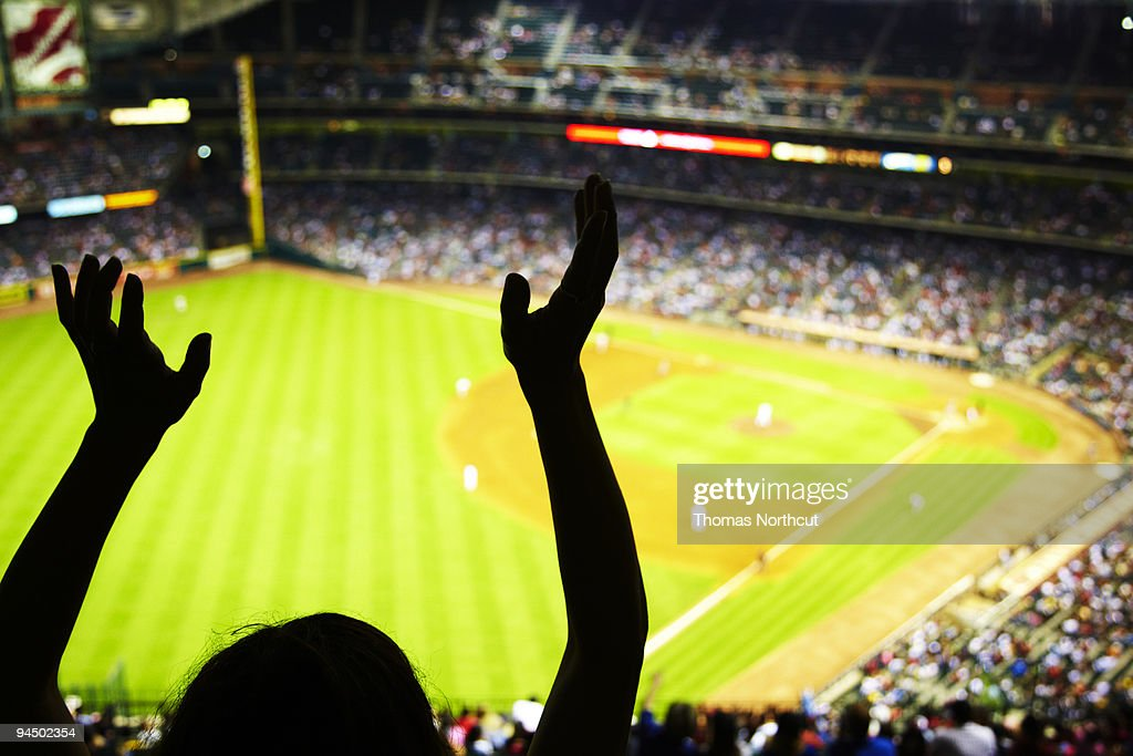 Silhouette of Baseball fan waving hands in the air : Stock Photo