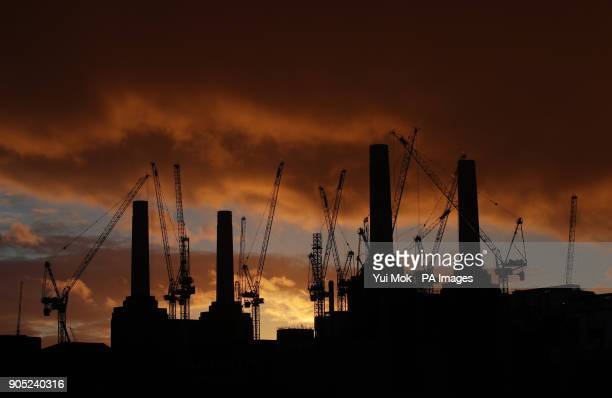 A silhouette of Battersea Power Station and the surrounding cranes at sunset in London